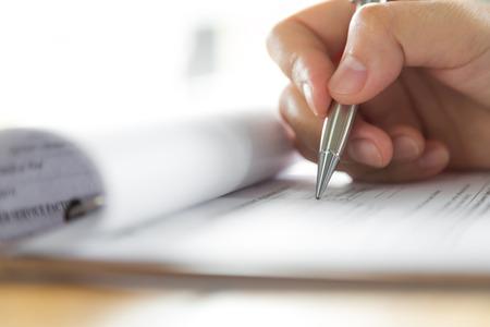 escribiendo: Mano con la pluma sobre el formulario de solicitud