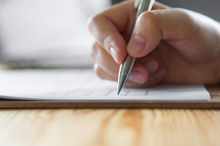mark pen: Hand with pen over application form Stock Photo