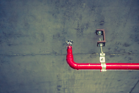 building safety: Fire sprinkler and red pipe  ( Filtered image processed vintage effect. )