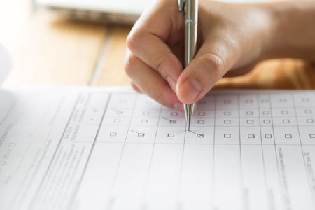 checklist: Hand with pen over application form Stock Photo