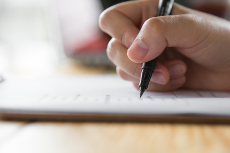 pen and paper: Hand with pen over application form Stock Photo