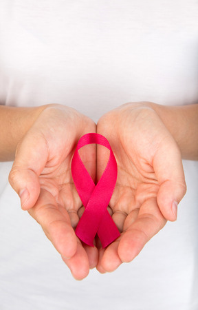aids: Female hands holding red AIDS awareness ribbon Stock Photo