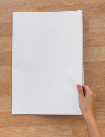 periodicos: Asimiento de la mano del periódico en blanco con el espacio vacío maqueta en madera de fondo