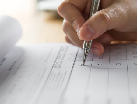 Hand with pen over application form Standard-Bild
