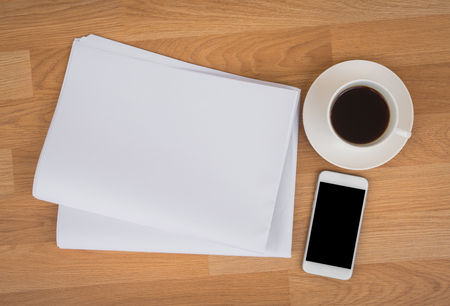 broadsheet: Blank Newspaper with empty space and coffee cup ,mobile phone mock up on wood background