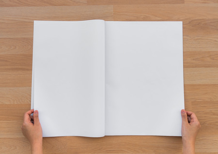 broadsheet: Hand hold Blank Newspaper with empty space mock up on wood background Stock Photo