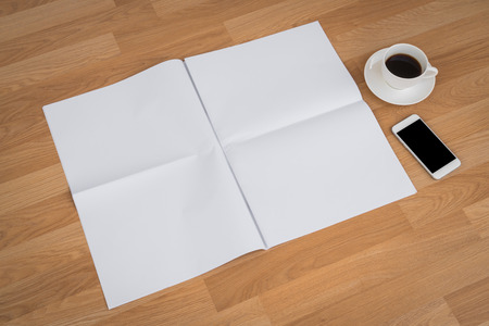 copy writing: Blank Newspaper with empty space and coffee cup ,mobile phone mock up on wood background