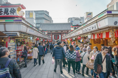 senso ji: TOKYO,JAPAN - 24 November  2015 :Tourists walk on Nakamise Dori in Sensoji shrine.Sensoji temple with a variety of traditional, local snacks and tourist souvenirs for centuries.