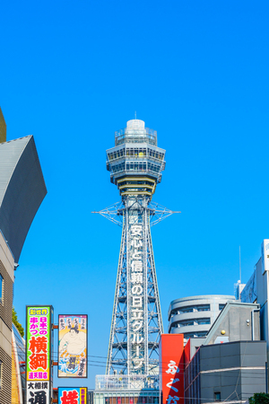 advertises: OSAKA, JAPAN - NOVEMBER 30, 2015: Tsutenkaku Tower in Shinsekai (new world) district with blue sky. It is a tower and well-known landmark of Osaka, Japan and advertises Hitachi.