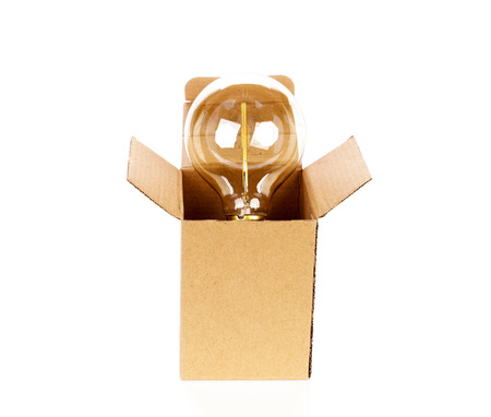 corrugated box: Glowing light bulb over open cardboard box