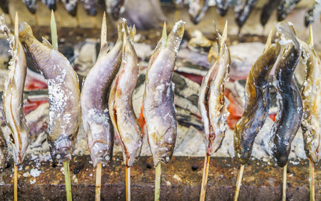 coal fish: Fish with salt being grilled outdoors in Japan