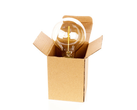 constraints: Glowing light bulb over open cardboard box