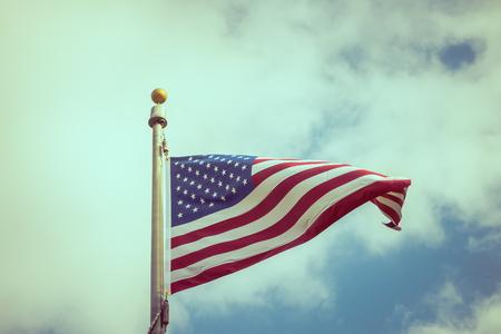 red flag up: American flag on blue sky ( Filtered image processed vintage effect. )