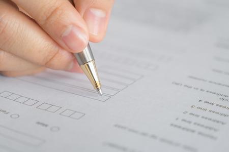 アプリケーションのフォーム上のペンを持つ手
