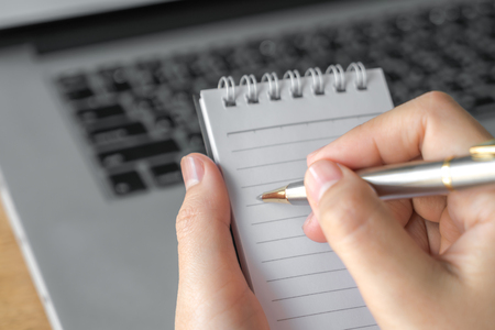 noting: Woman  hand using a pencil noting over laptop