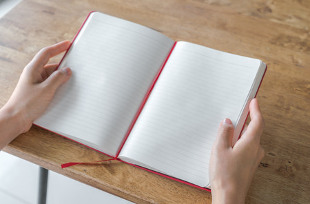 two page spread: Hands open Blank catalog, magazines,book mock up on wood table Stock Photo