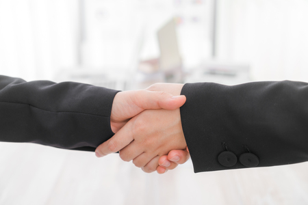 altogether: Business people shaking hands over laptop Stock Photo