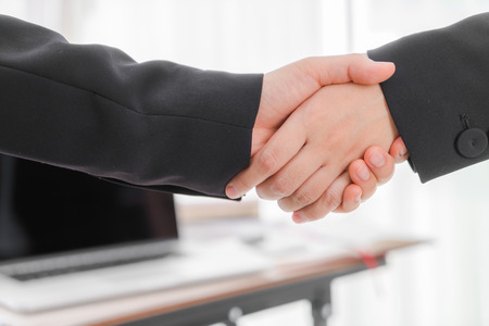 unanimous: Business people shaking hands over laptop Stock Photo