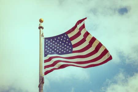 processed: American flag on blue sky ( Filtered image processed vintage effect. )