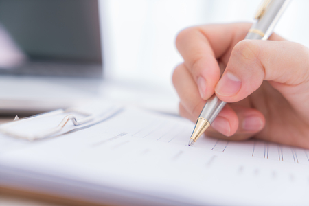 poll: Hand with pen over application form Stock Photo