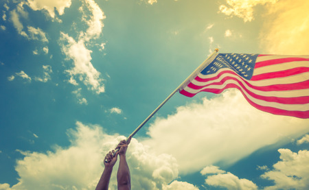 patriotism: American flag with stars and stripes hold with hands against blue sky Stock Photo