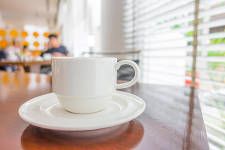 cappuccino foam: Coffee in white cup on wood table