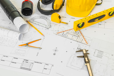 yellow helmet: Construction plans with yellow helmet and drawing tools on blueprints