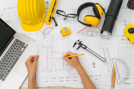 Hand over Construction plans with yellow helmet and drawing tools on blueprints Stock Photo