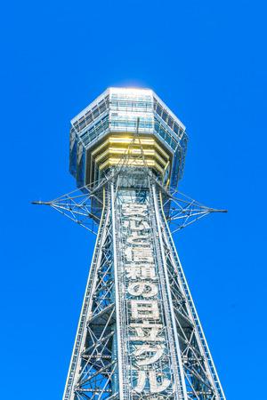 OSAKA, JAPAN - NOVEMBER 30, 2015: Tsutenkaku Tower in Shinsekai (new world) district with blue sky. It is a tower and well-known landmark of Osaka, Japan and advertises Hitachi.