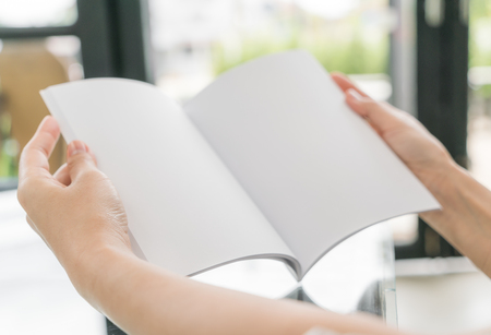 two page spread: Hands open book on table