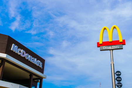 mcdonalds: Khonkaen Province, Thailand - December 20, 2015 : McDonalds logo on blue sky McDonalds Corporation is the worlds largest chain of hamburger fast food restaurants. Editorial