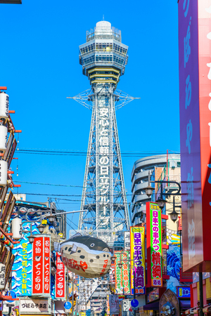 pez globo: OSAKA, JAPAN - NOVEMBER 30, 2015: Tsutenkaku Tower in Shinsekai (new world) district with blue sky. It is a tower and well-known landmark of Osaka, Japan and advertises Hitachi.