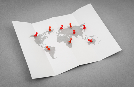 red pin: Paper folded world map  with red Pin Pointer