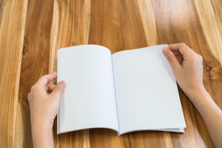 two page spread: Hands open book on wood table Stock Photo
