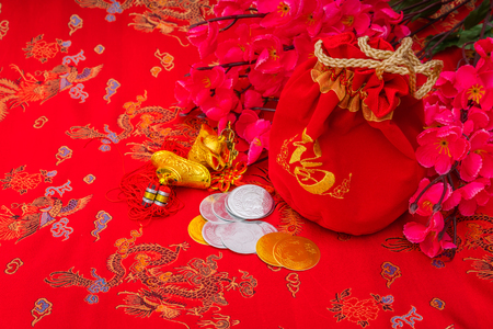 monete antiche: Chinese new year decoration on red fabric background ,Chinese characters text means: rich, successfully, happiness, peace, riches and honour, auspicious , good luck