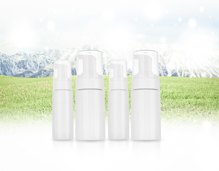 desaturated: Cosmetic product  for cream, foam, shampoo. on  Panorama of Mountain Snow  Landscape with green grass