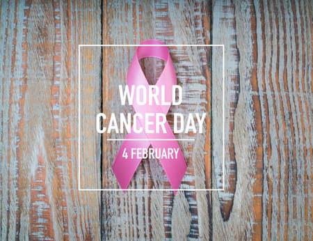 World cancer day : Breast Cancer Awareness Ribbon on wood Background