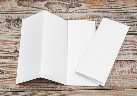 Four - fold white template paper on wood texture Stockfoto