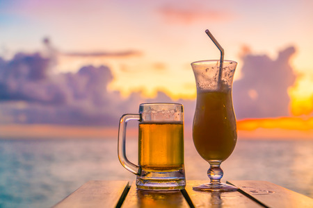 A glass of beer with Beautiful tropical Maldives island Stock Photo