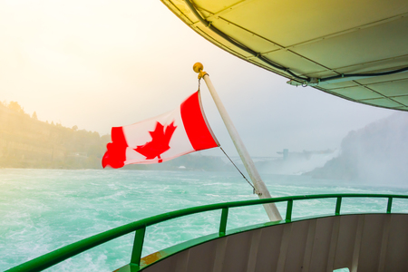 Canadian flag on a boat at Niagara Falls  ( Filtered image processed vintage effect. ) Stock Photo