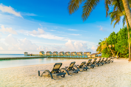 Beach chairs in Maldives island with water villas at the sunrise time Stock Photo