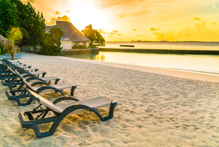 Beach chairs in Maldives island at the sunrise time