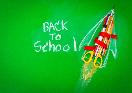 Rocket made from School supplies on Green chalkboard  Back to school background