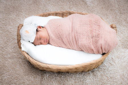 Cute sleeping newborn girl on a blanket.