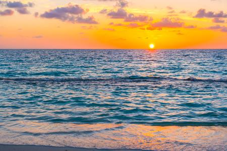 Hermosa puesta de sol con cielo sobre el mar en calma en la isla tropical de Maldivas Foto de archivo