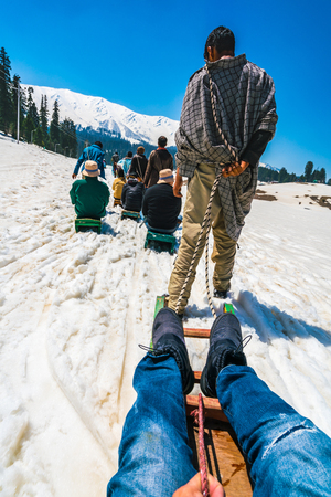 Sled driver carry the tourist on snow sled up to the hill,Kashmir state, India .