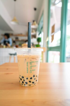 Milk Bubble Tea with Tapioca Pearls on wooden table.