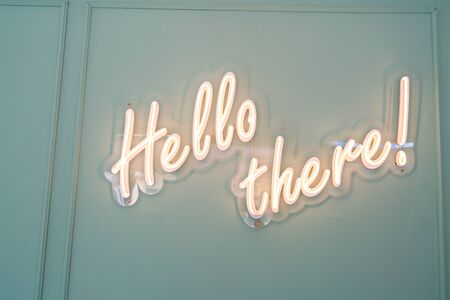 Neon glowing sign with word Hello there and green wall.