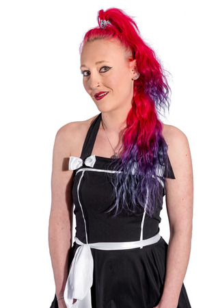 Woman with red hair and petticoat dress posing against white background
