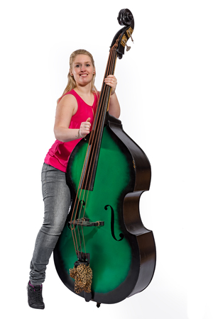 Female musician wearing red shirt plays on a double bass in front of white background 写真素材